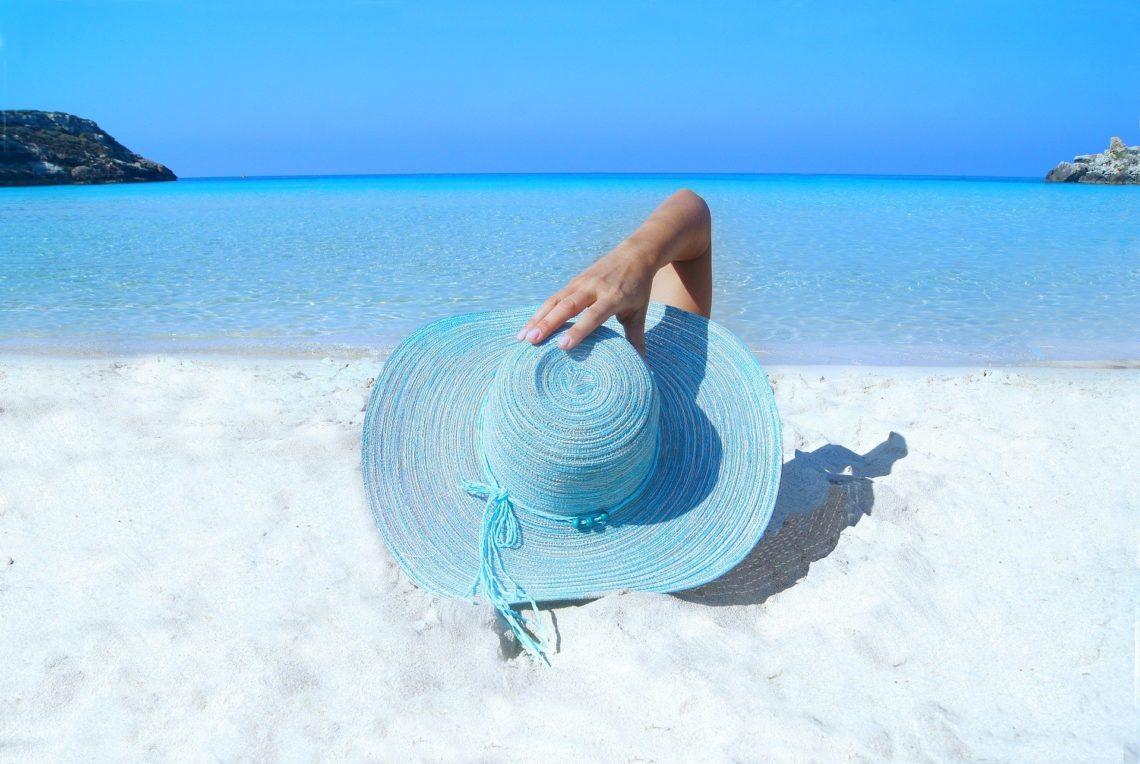 femme à la plage portant un chapeau et prenant le soleil.